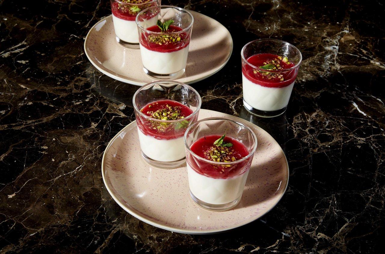 Malabi dessert in kleinen Gläsern auf Tellern